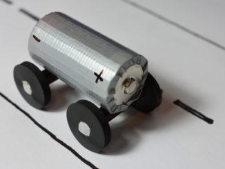 Modell zur Veranschaulichung des Themas Elektromobilität und E-Auto: Eine kleine Batterie auf Gummirädern fährt eine gezeichnete Straße entlang.