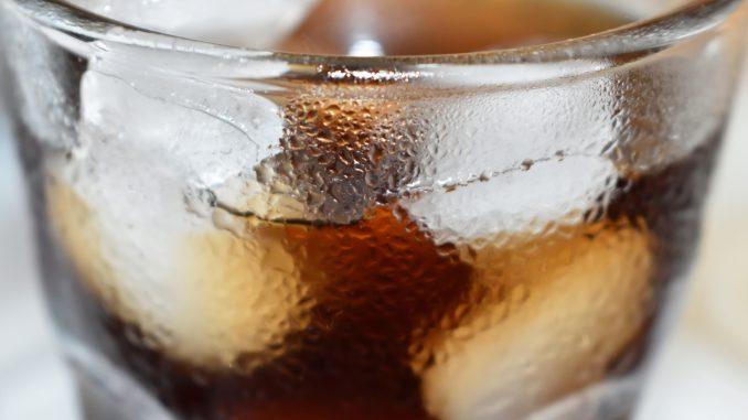 Erfrischender Genuss: Ein Glas Cola mit Eiswürfeln.
