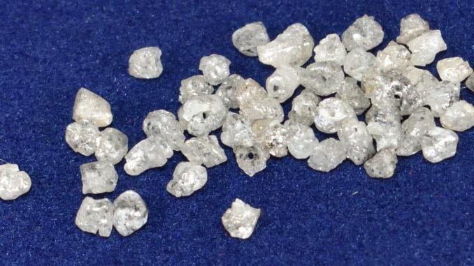 Auch ungeschliffen ein faszinierender Anblick: Rohdiamanten (hier mit gebohrtem Loch zum Auffädeln als Kette).